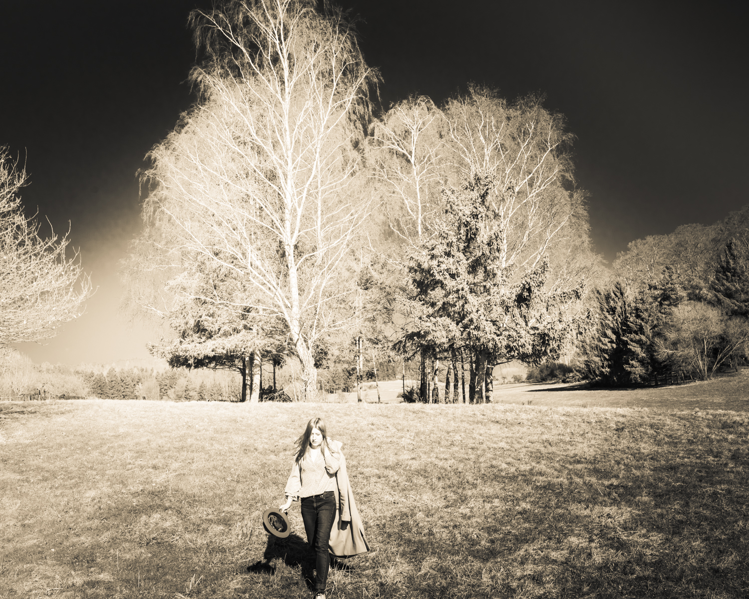 girl in nature in front of trees